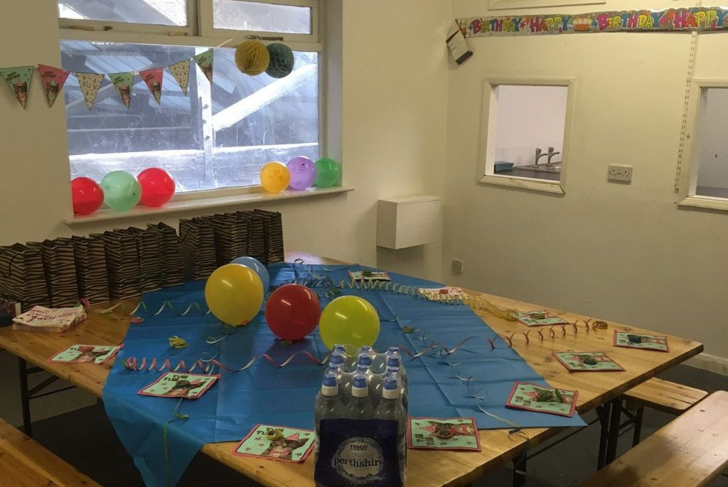 The party room has tables, benches and a small kitchen