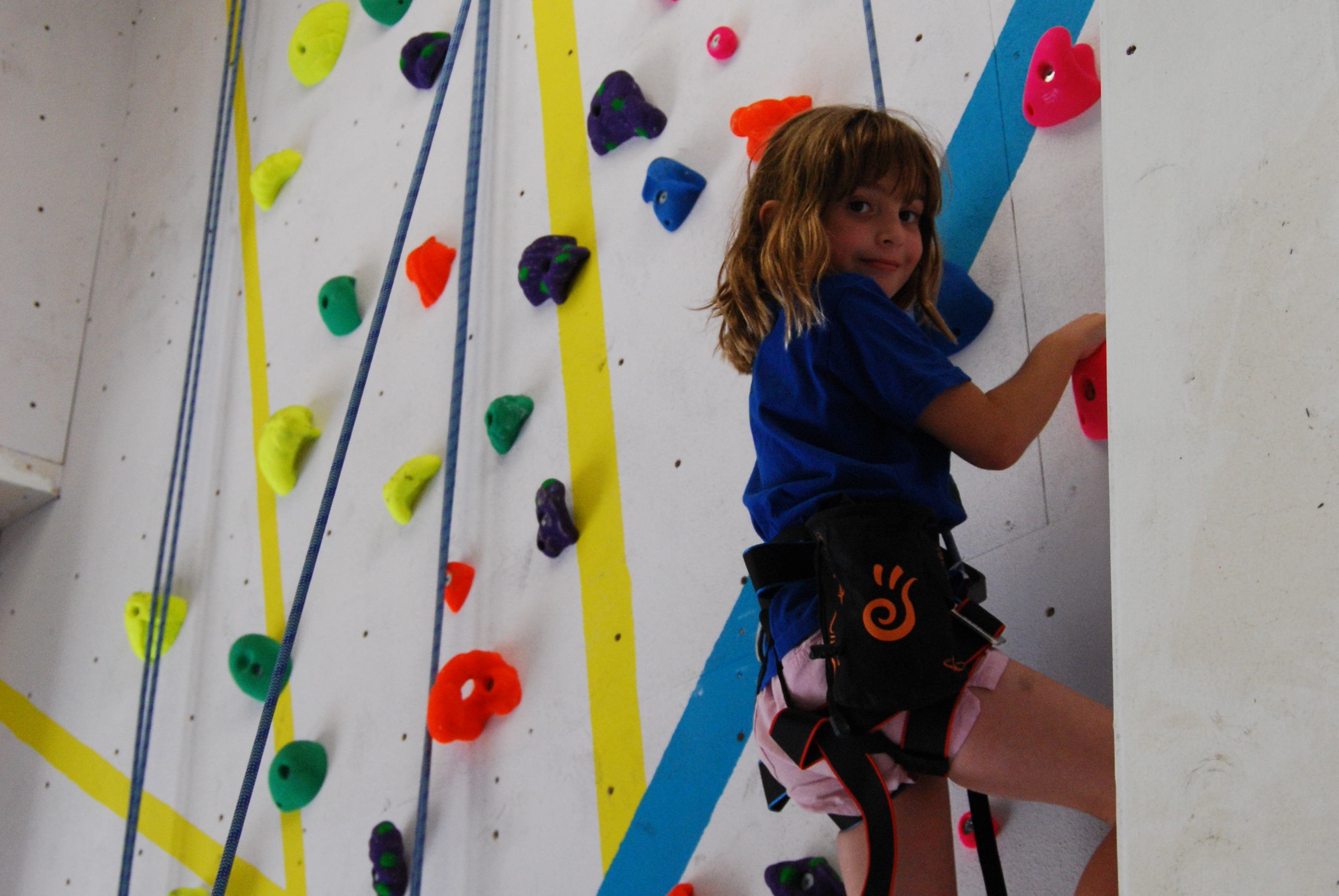 Girl climbing on the roped wall